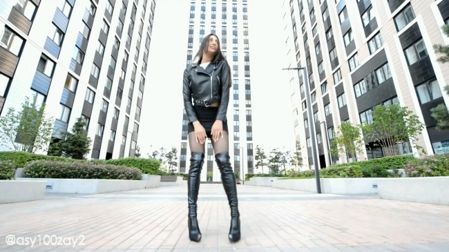 Walking In Overknee Boots And Leather Mini Skirt
